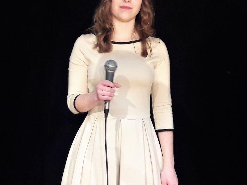 Na zdjęciu wokalistka MCK - Julianna kołodziejczyk. Wokalistka w sukni z mikrofonem w ręku