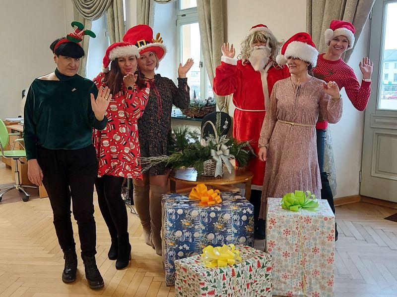na zdjęciu sześć osób w czapkach mikołaja a przed nimi trzy duże prezenty