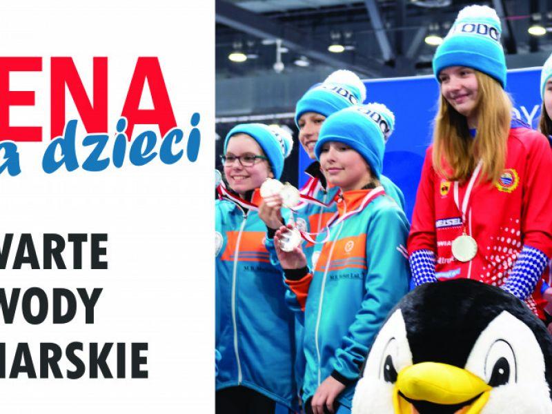 Na zdjęciu baner zawodów Arena dla Dzieci - otwartych zawodów łyżwiarskich. Na zdjęciu grupa udekorowanych medalami młodych łyzwiarzy pozująca do fotografii z pingwinem - maskotką Areny lodowej w Tomaszowie Mazowieckim