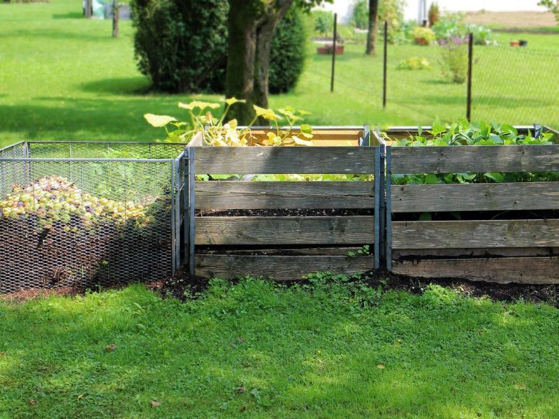 Na zdjęciu nprzydomowy kompostownik. Dwie skrzynki drewniane oraz jedna siatkowana, w środku resztki owoców