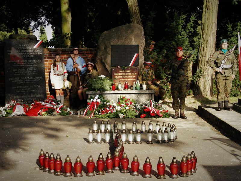Na zdjęciu warta honorowa pod obeliskami poświęconymi ZWZ-AK i komendantom AK. Przed obeliskami ułożone 63 biało-czerwone znicze