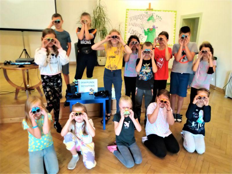 Na zdjęciu dzieci podczas Wakacyjnych Warsztatów w bibliotece pozują do fotografii z samodzielnie wykonanymi lornetkami, przez które patrzą
