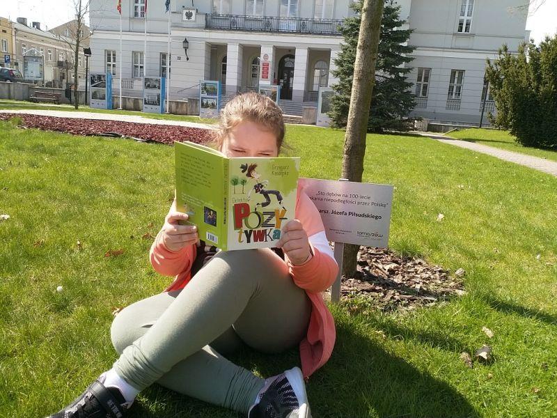 Na zdjęciu uczennica SP nr 12 czytająca ksiąkę przed gmachem Urzędu Miasta w Tomaszowie Mazowieckim. Dziewczynka trzyma w ręku ksiązxkę w tle budynek Urzędu Miasta