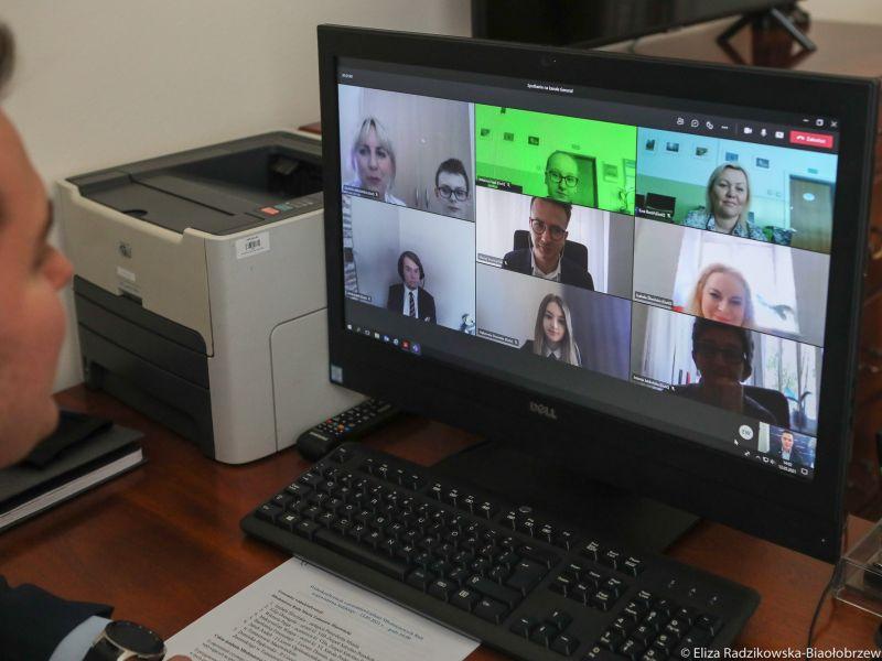 mężczyzna siedzi przed monitorem w którym widać kilka osób