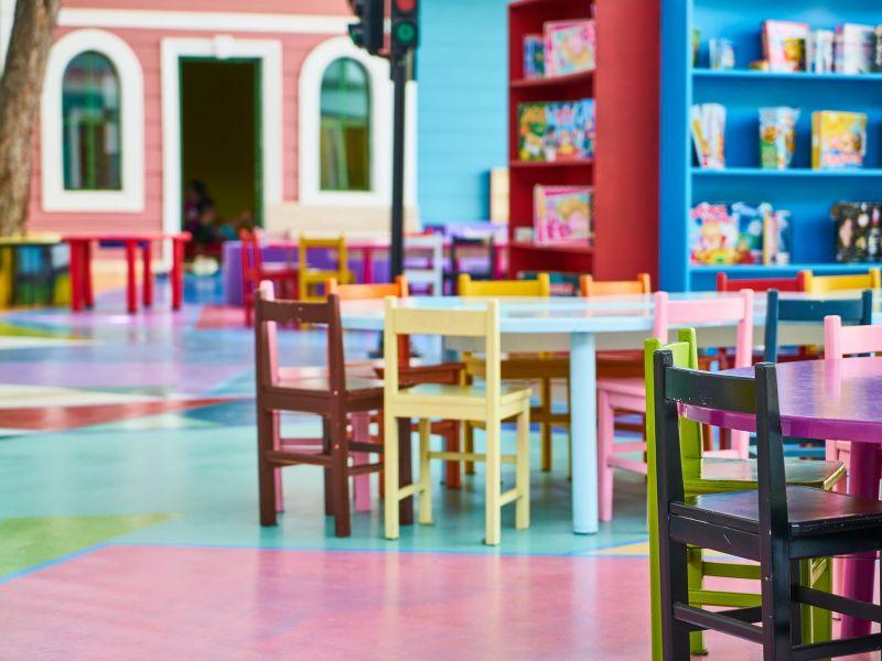 Na zdjęciu sala przedszkolna wyposażona w kolorowe stoliki i krzesełka i półki z zabawkami