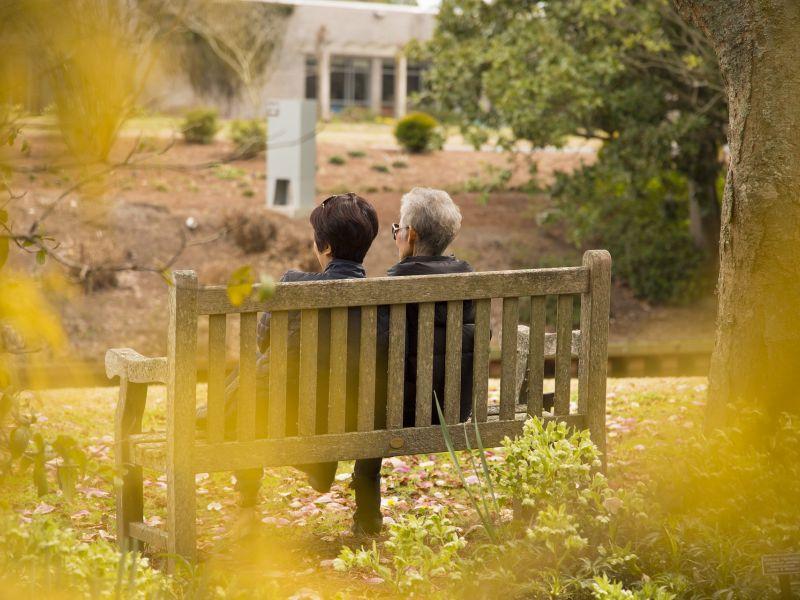 Na zdjęciu dwójka seniorów siedząca na ławce, aura jesienna