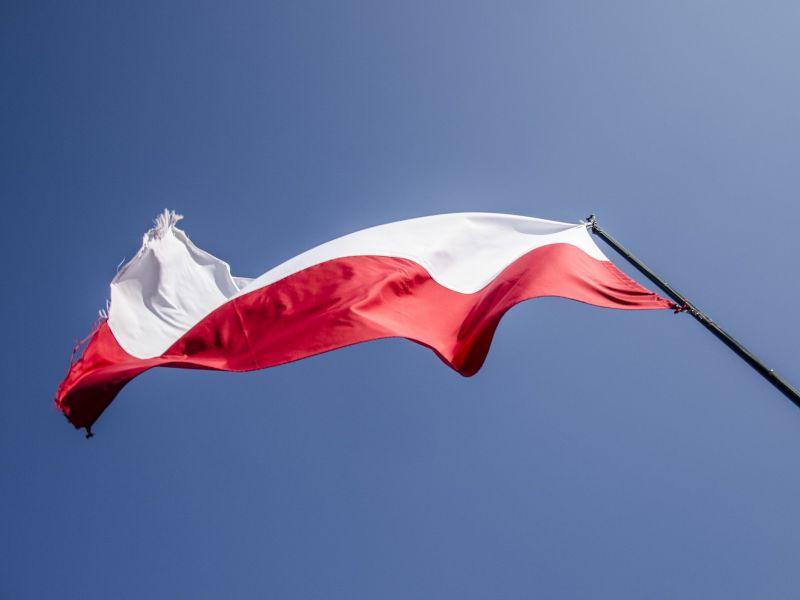 Na zdjęciu flaga biało-czerwona na maszcie, sfotografowana