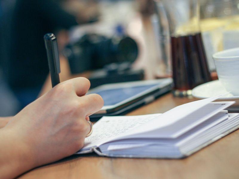 Na zdjęciu widać dłoń trzymającą długopis, otwarty zeszyt, w tle leży tablet i filiżanka z napojem