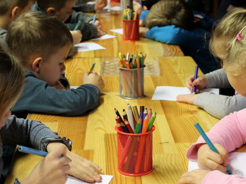 Na zdjęciu przedszkolaki podczas zajęć plastycznych. Zajęcia plastyczne, kartony i kredki na stole
