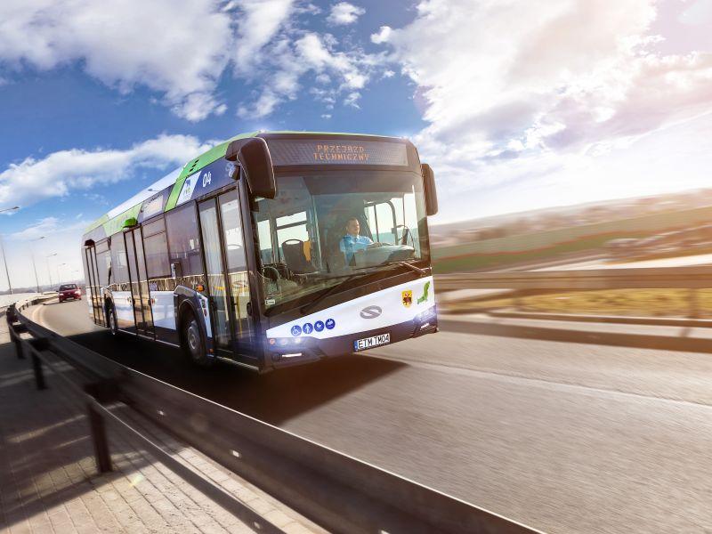 Na zdjęciu widać autobus MZK przejeżdżajacy przez tamę Zalewu Sulejowskiego. Zza przedniej szyby widać kierowcę autobusu, w tle akwen zalewu