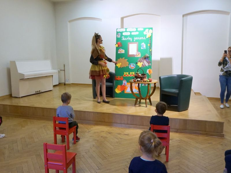 na zdjęciu widać: salę z sceną na której stoi białe pianino oraz kobieta przebrana za panią jesień pokazuje reką obrazki z tablicy stojącej na scenie,  pięcioro dzieci siedzących na czerwonych krzesełkach oraz  jedna kobieta robiąca zdjęcia telefonem