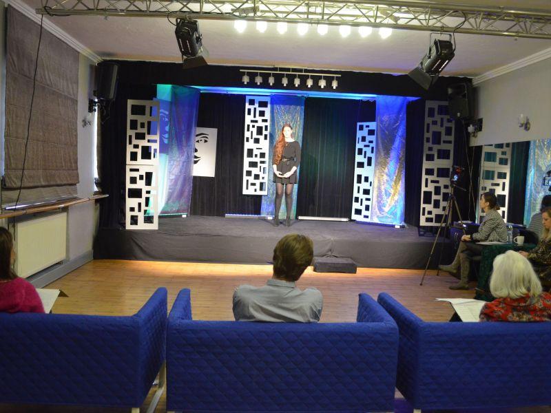 Na zdjęciu recytatorka startująca w konkursie recytatorskim Miejskiego Ośrodka Kultury. Dziewczyna recytuje tekst na scenie, występu wysłuchuje jury siedzące we fotelach