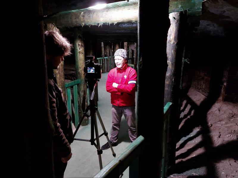Na zdjęciu widać reportera stojącego przed kamerą. Reporter ubrany w czerwonej bluzie turystycznej, przed nim włączona kamera na stojaku. Materiał jest kręcony w podziemnej trasie turystycznej Groty Nagórzyckie, widać wewnętrzne ożebrowanie trasy turystyc