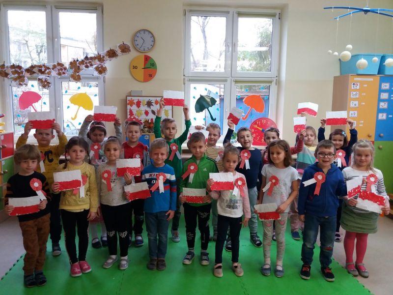 Na zdjęciu widać dzieci w wieku przedszkolnym z kotylionami biało-czerwonymi i biało-czerewonymi flagami wykonanymi na zajęciach plastycznych z okazji Święta Niepodległości. Zdjęcie wykonano w pracowni przedszkolnej.