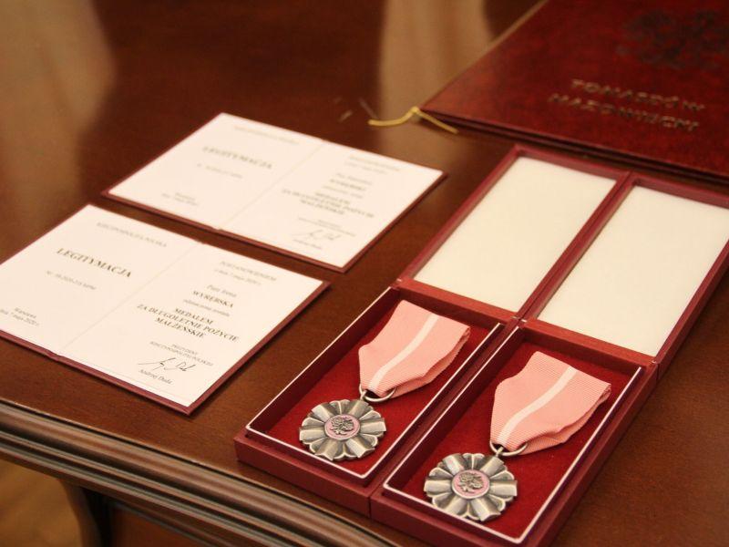 na brązowym stole leżą dwa medale oraz dwie legitymacje