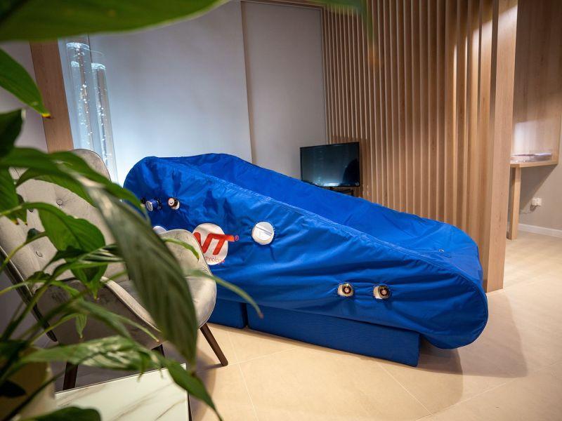 zdjęcie przedstawia komorę hiperbaryczna w kolorze niebieskim na pierwszym planie liscie kwiatów, fotel oraz telewizor