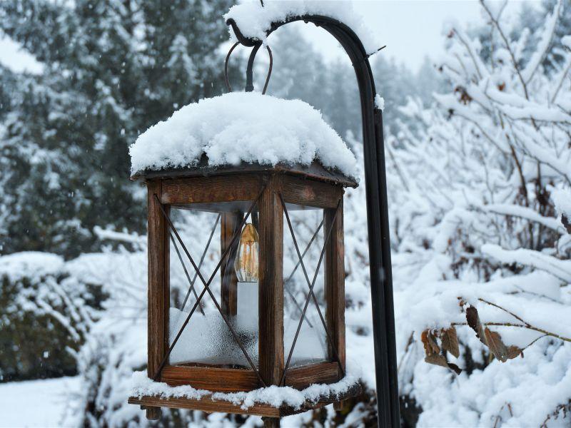 Na zdjęciu ogrodowa lampka z ośniezonym daszkiem, w tle silna zimowa aura, na gałęziach mnóstwo śniegu