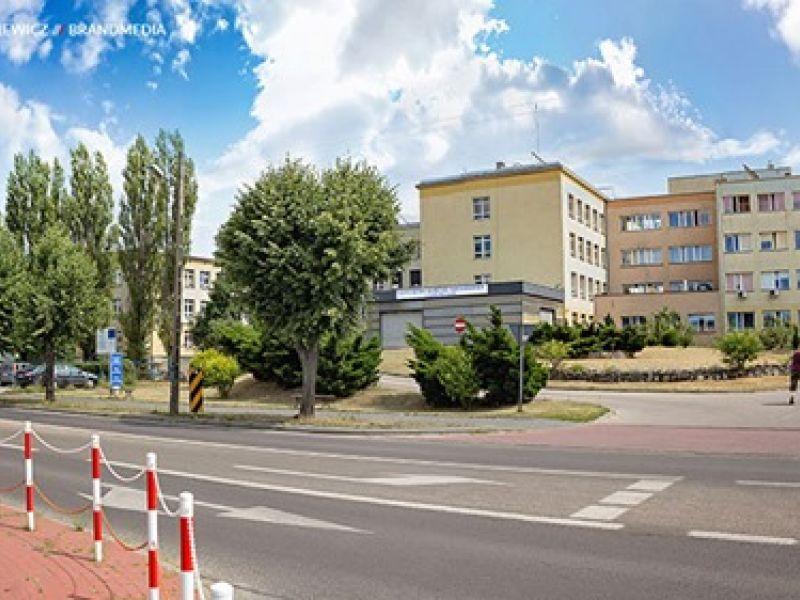 Ulica, w tle duży, jasny budynek - szpital, przy pasie drogowym zielone drzewa