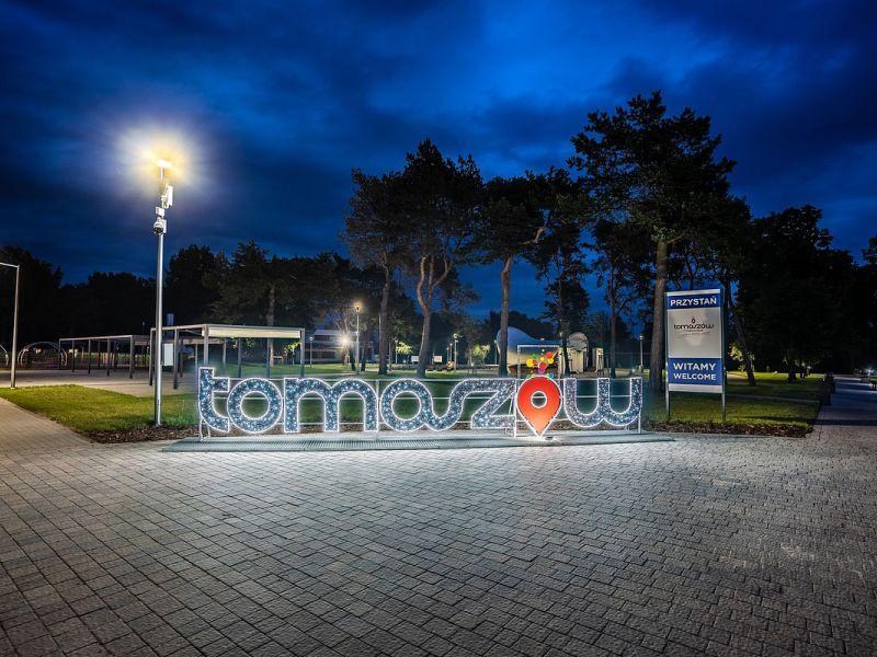 Na zdjęciu przystań miejska nad Pilicą nocą, na pierwszym planie podświetlony napis z logiem miasta