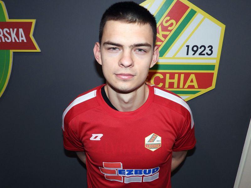 Na zdjęciu nowy zawodnik Lechii Tomaszó pozujący do zdjęcia na tle klubowego logo