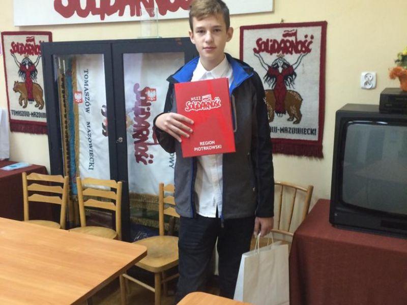 na zdjęciu jest chłopiec trzymajacy czerwoną teczkę oraz białą torebkę. chłopiec stoi w pomieszczeniu z stołami i krzesłami na ścianie wisi baner z nazwą Solidarność