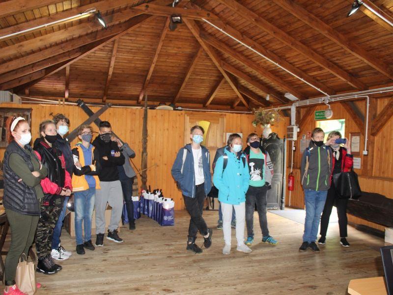 zdjęcie przedstawia 12 osób stojących wewnętrz drenianego budynku patrząych w jedno miejsce