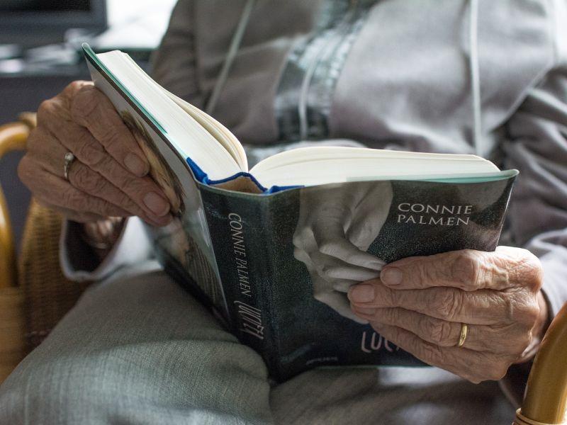 na zdjęciu widać ręce starszej kobiety trzymające książkę