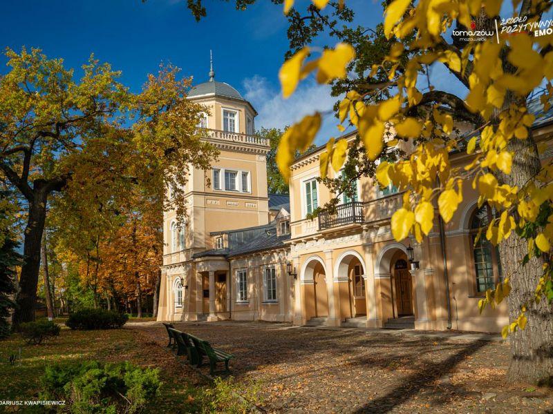 na zdjęciu gmach Muzeum w tomaszowie Mazowieckim w antruazu jesiennym. Opadłe liście na placu przed budynkiem, pożółkłe licie jna drzewach przed Muzeum.