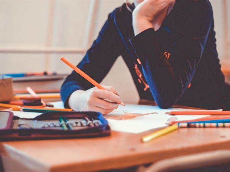 W kadrze widoczna uczennica trzymajaca ołówke, obok leży piórnik i przybory szkolne