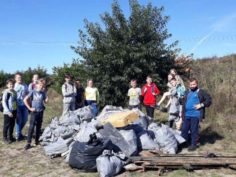 Na zdjęciu uczniowie ze szkoły podstawowej, w tle zebranych w worki śmieci, które zostały zebrane i sprzątnięte z lasu