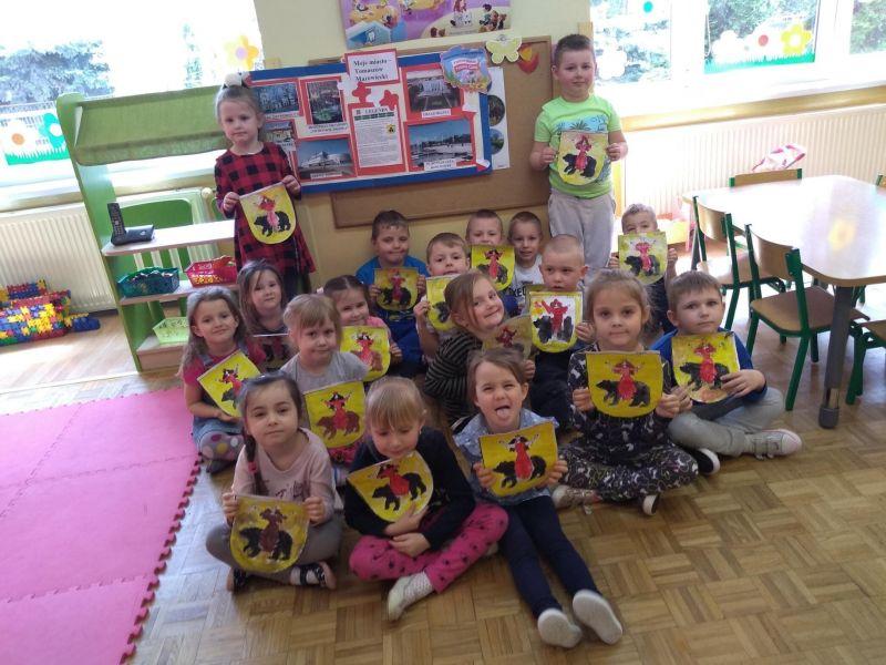 Na zdjęciu przedszkolaki pozują siedząc na podłodze w pracowni i prezentując wykonane przez siebie place plastyczne - herb Tomaszowa Mazowieckiego