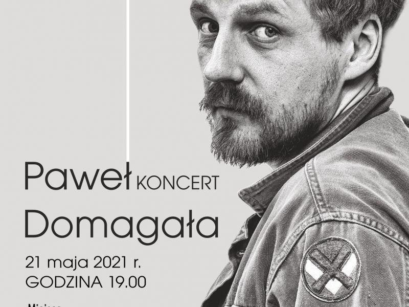 Na zdjęciu plakat koncertu Pawła Domagały w Arenie Lodowej ze zmienioną datąm koncertu (Covid-19). Na zdjęciu artysta w kurtce jeansowej, obok informacje o koncercie