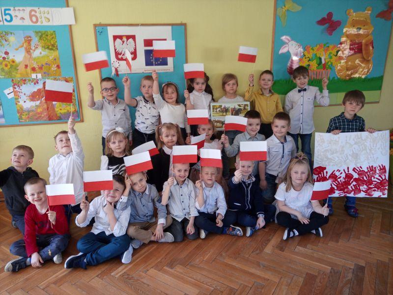 Na zdjęciu przedszkolaki z Przedszkola nr 8 pozujący do zdjęcia z samodzielnie wykonanymi biało-czerwonymi chorągiewkami