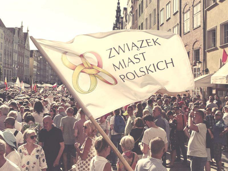 Na zdjęciu flaga Związku Miast Polskich, w tle tłum ludzi na deptaku dużego miasta