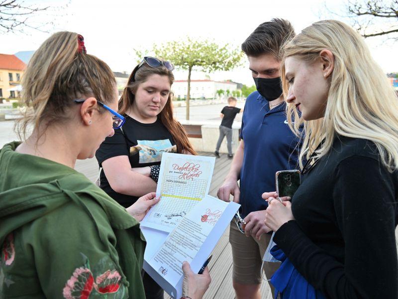 Na zdjęciu uczestnicy gry ulicznej MCK zapoznają się z mapami i zagadkami na płycie placu Kościuszki