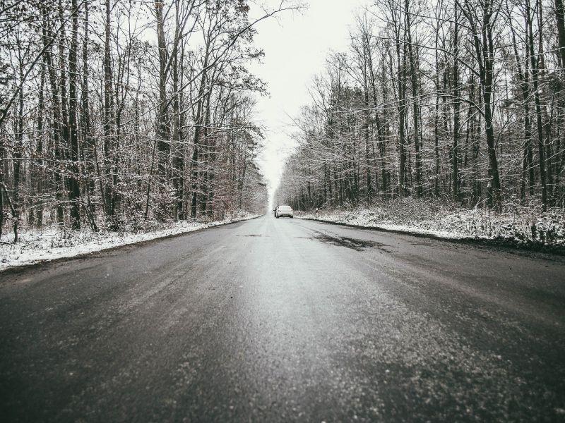 Na zdjęciu nawierzchnia oblodzonej drogi, wokół oszroniony las