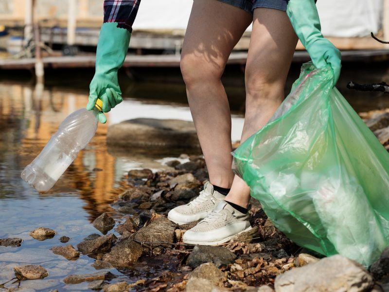 Na zdjęciu widać nogi schylającego się człowieka, wyciągającego butelkę plastikową z wody