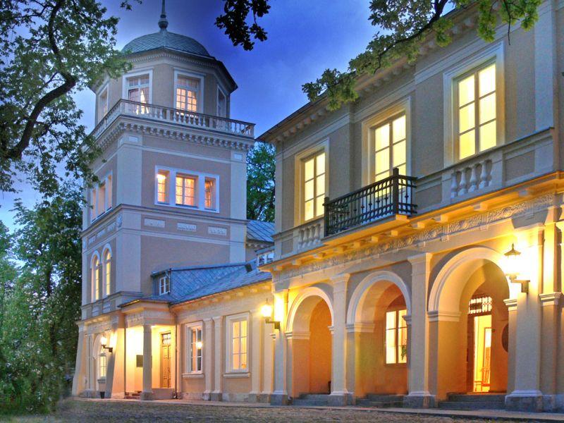 na zdjęciu widać budynek muzeumz zapalonymi światłami, drzewa z zielonymi liściami