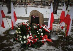 pomnik w  otoczeniu flag oraz biało czerwonych wieńcy